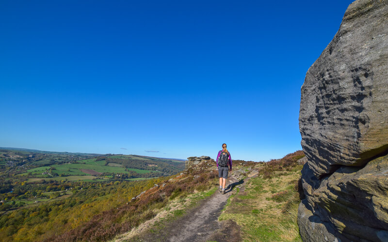 Person walking rock on right and blue skies