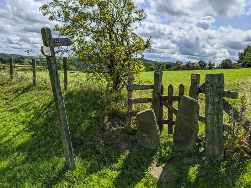 Stone stile, gate and signpost
