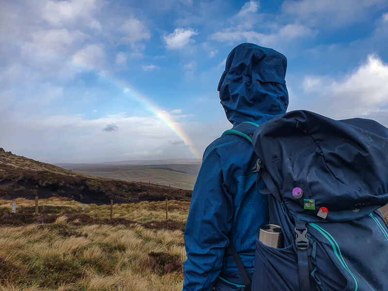 Person standing with backpack on and rainbow
